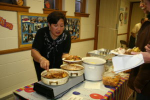 2016 UPC Ethnic Food Fair co-chair Vera Heitink serves an Indonesian dish she prepared at a previous UPC Ethnic Food Fair.